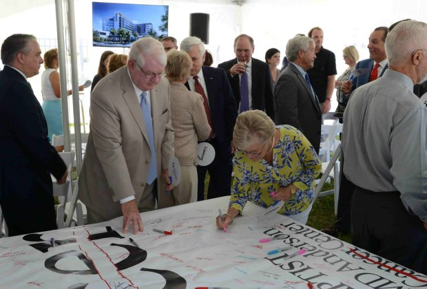 Carter and Cheryl Bryan, philanthropists, sign the banner in recognition and remembrance of the groundbreaking day for the hospital system.