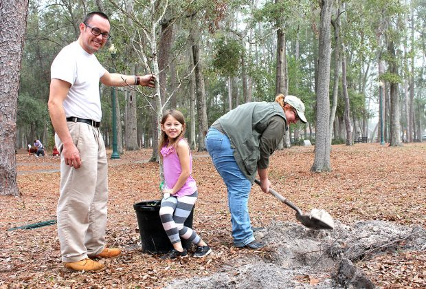 "Tom Caron and daughter, Maggie, ""help"" good friend Lori Strain plant a sweetgum tree in Boone Park."