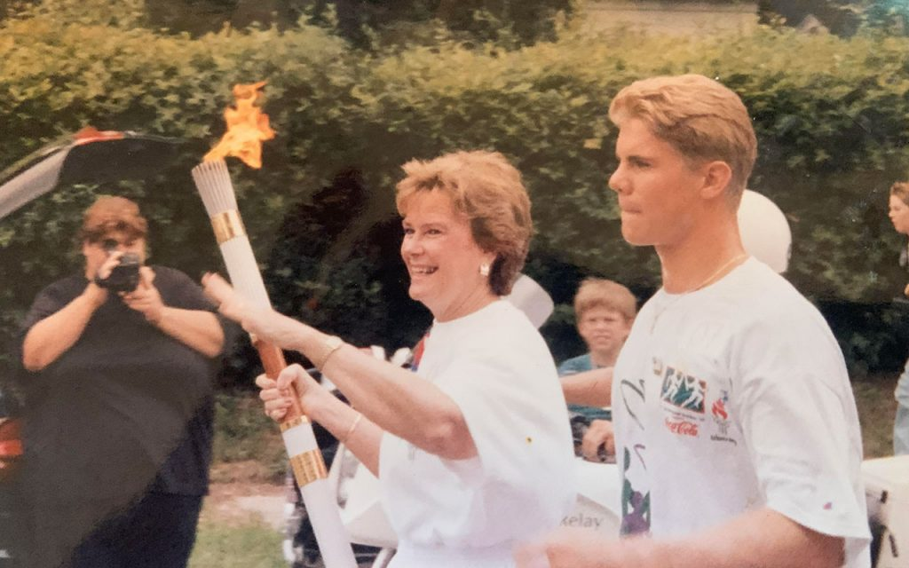 Sissy carrying Olympic torch with escort Scott Blinkhorn